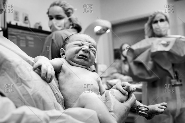 Doctor holding newborn baby in the delivery room