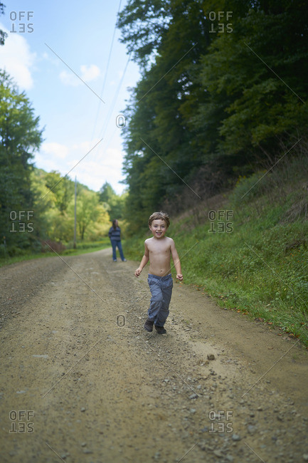 Little boy in jeans walking on a dirt road