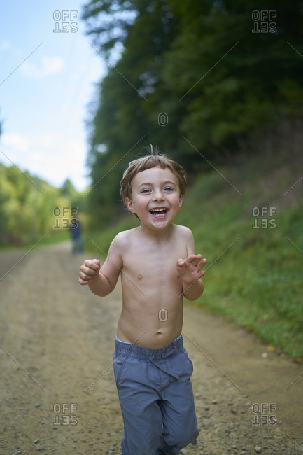 Little boy playing on a dirt path in the woods