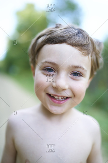 Little boy with brown hair and no shirt smiling