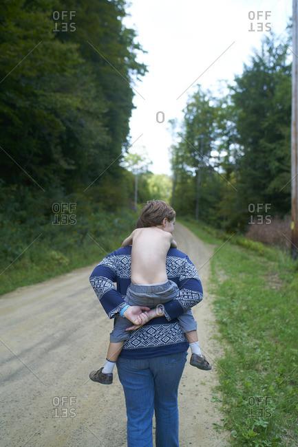 Woman carrying a little boy piggyback on a dirt road