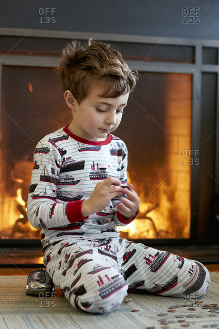 Little boy in pajamas counting money beside a fireplace