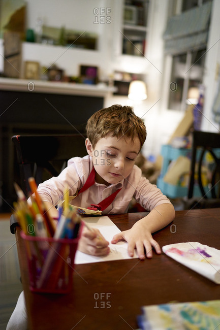 Little boy sitting at a table coloring on paper