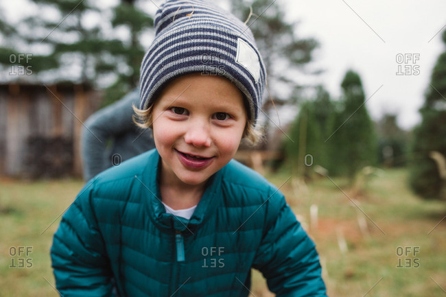 Boy in a down jacket and toboggan smiling