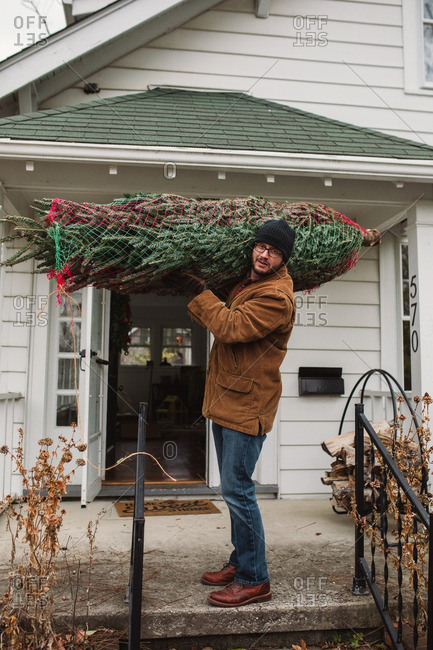 Man carrying a Christmas tree on his front porch
