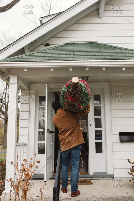 Man carrying a Christmas tree through the front door of his home