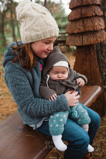 Girl sitting on a bench holding her baby sister in her lap