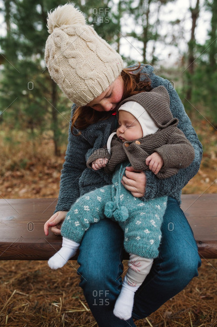 Girl holding her sleeping baby sister in her lap on an outdoor bench