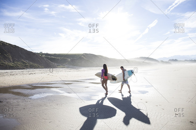 Couple carrying surfboards walking on the beach