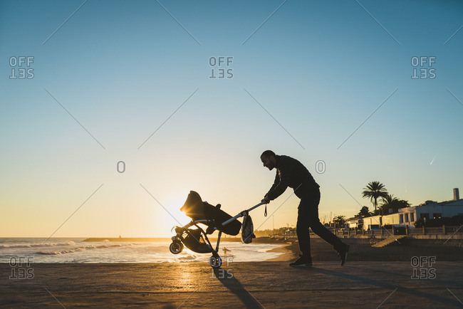 Man walking with a stroller on the seashore at sunset