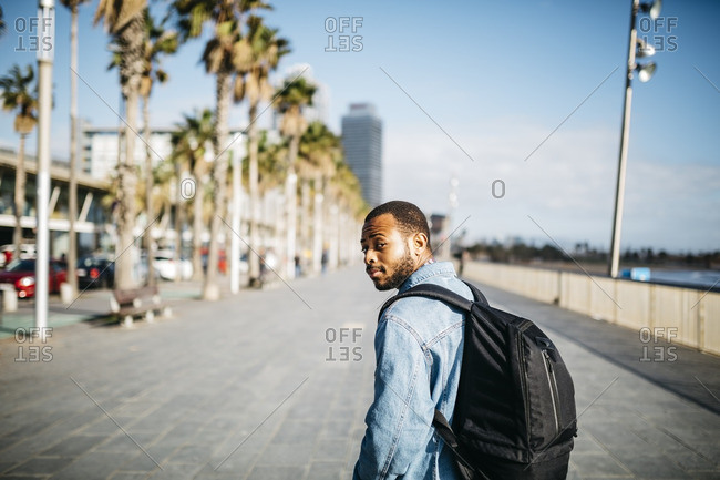 Spain Barcelona young man with backpack walking on beach promenade