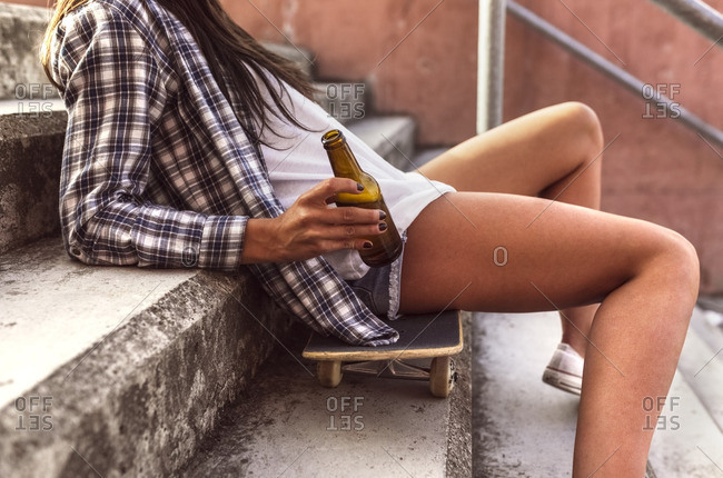Young woman sitting on skateboard holding a beer bottle