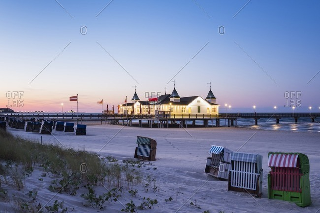 Germany Usedom Ahlbeck view to lighted sea bridge with hooded beach chairs in the foreground at dusk