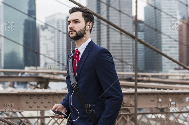 USA New York City businessman with cell phone and ear buds on Brooklyn Bridge