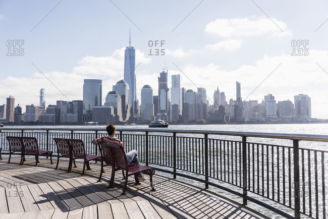 USA woman sitting on bench at New Jersey waterfront with view to Manhattan