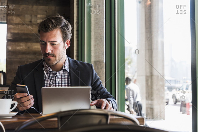 Businessman using tablet and cell phone in a cafe