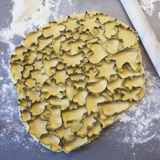 Many cookie cutters on rolled out cookie dough