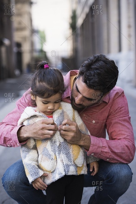 Father dressing daughter in warm coat