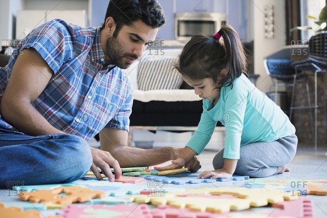 Father and daughter sitting on floor playing with children's puzzle
