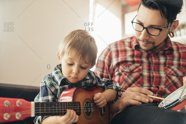 Father and son playing toy musical instruments