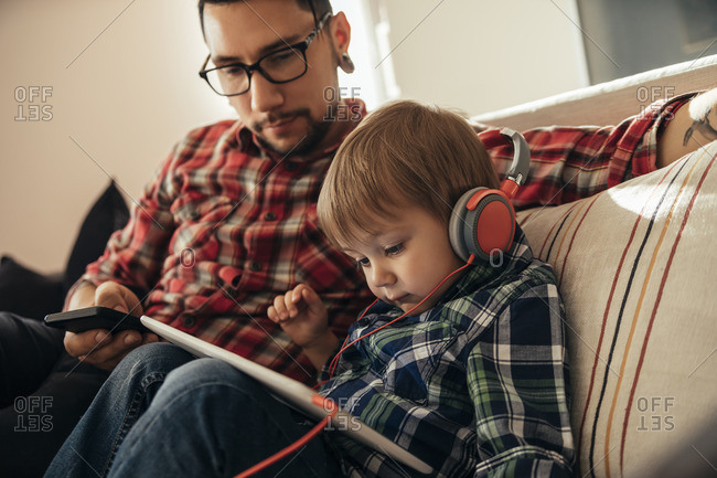 Father and son on couch using tablet and wearing headphones