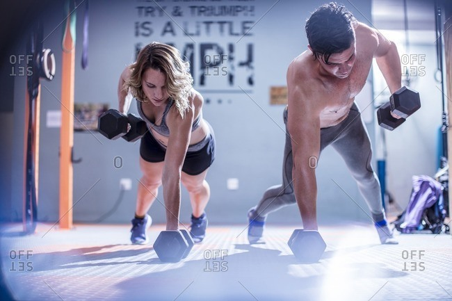 Young man and woman doing dumbbell press ups in gym