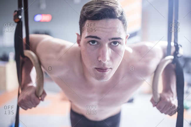Young man exercising at rings in gym