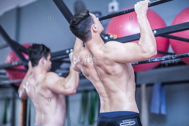Two young men doing pull-ups in gym