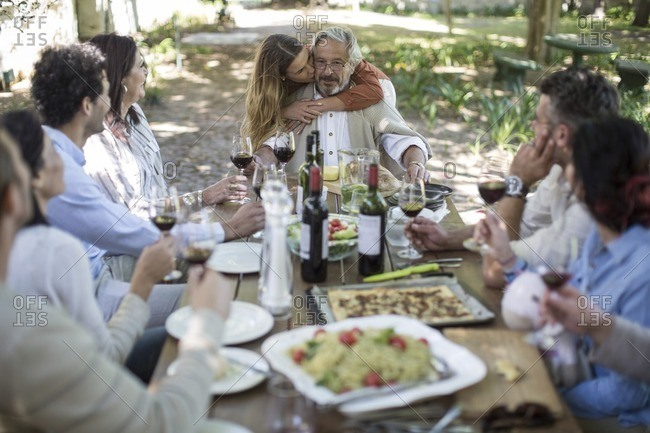 Adult daughter embracing father during lunch in garden