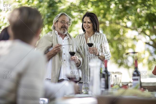 Senior couple raising a toast  during family lunch in garden