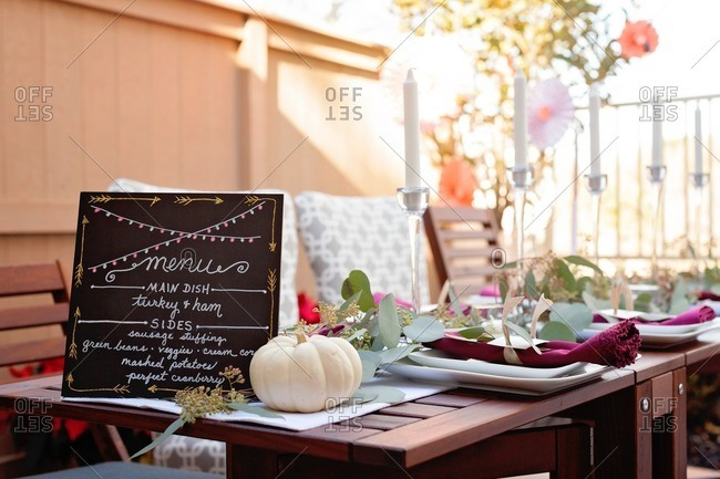 Table with menu at an outdoor Thanksgiving dinner party
