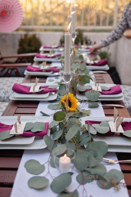 Person setting table for an outdoor Thanksgiving dinner party