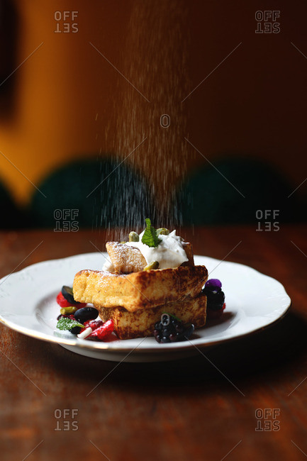 French toast being sprinkled with powdered sugar