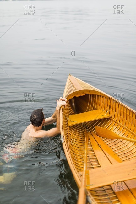 A young man swims next to a small antique wooden row boat in the St. Lawrence River in upstate New York's 1000 Islands