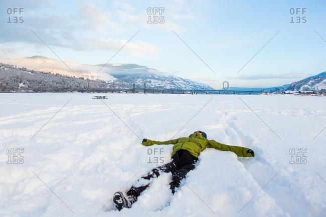 A young woman lies on her back in the snow in the Columbia River Gorge
