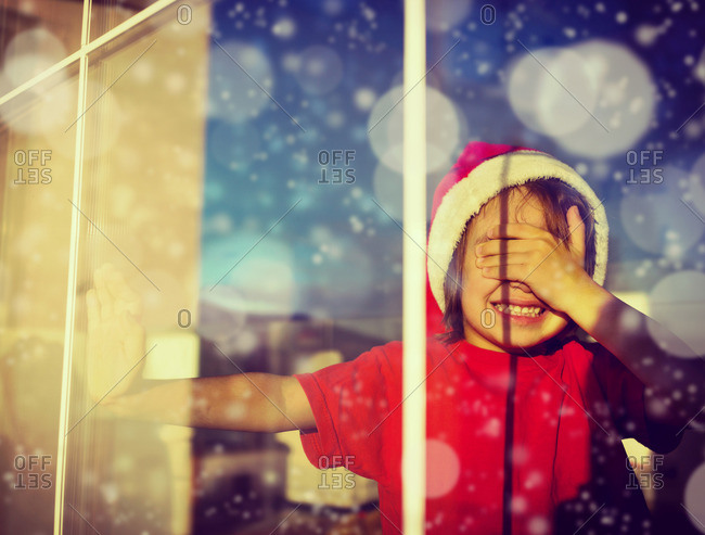 Child wearing a Santa hat and covering his eyes in a window