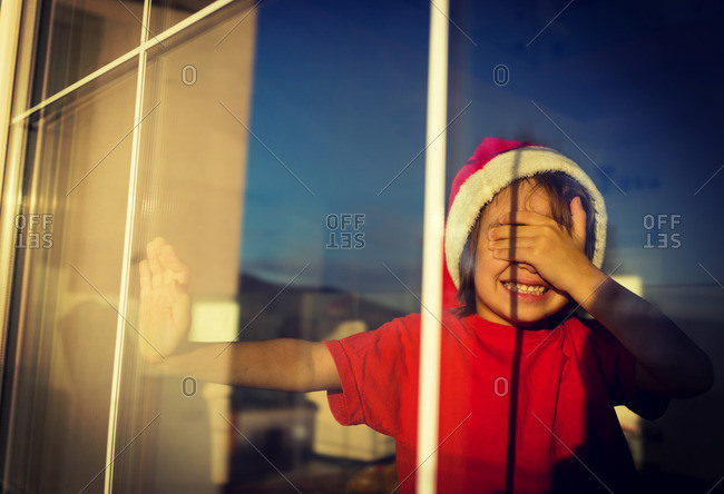 Boy wearing a Santa hat and covering his eyes in a window