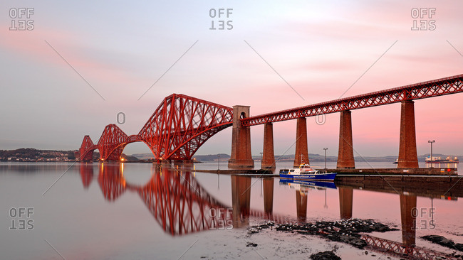 Loch Lomond, Scotland - January 5, 2017: Long exposure of the Forth rail bridge reflecting on the Firth of Forth during a colorful Sunset.