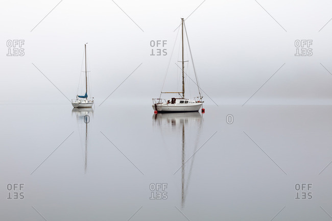 Loch Lomond, Scotland - January 21, 2017: Two sailing boats reflecting on the calm mist covered water of Loch Lomond in the morning light.