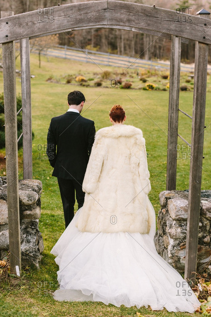 Back view of bride and groom walking through garden arbor