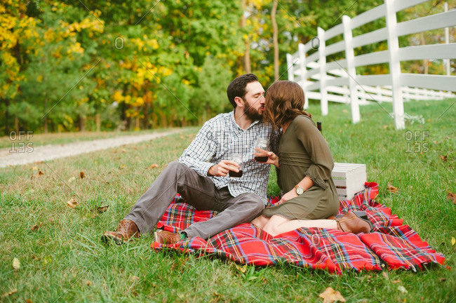 Couple kissing with drinks on blanket