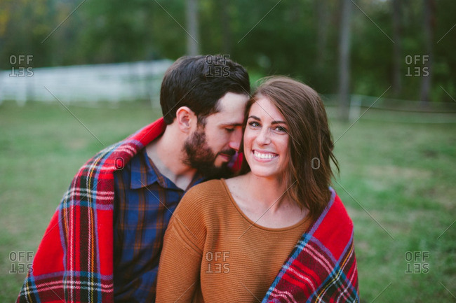 Smiling woman with man under blanket