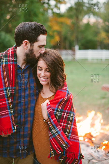 Loving couple wrapped in a blanket