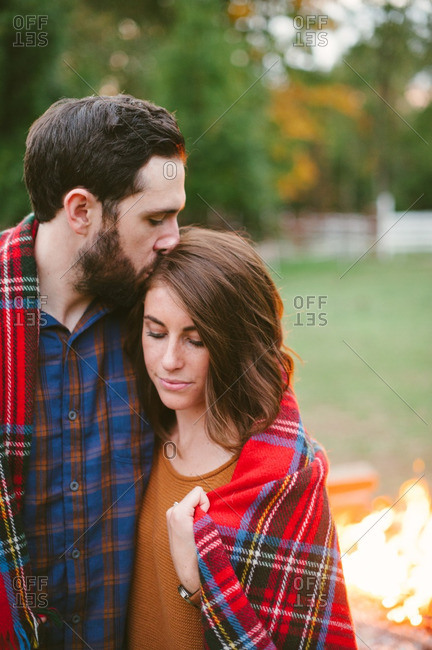 Loving couple with blanket in farmland