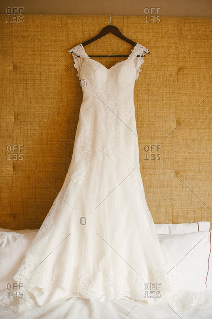 Bridal dress hanging over a bed