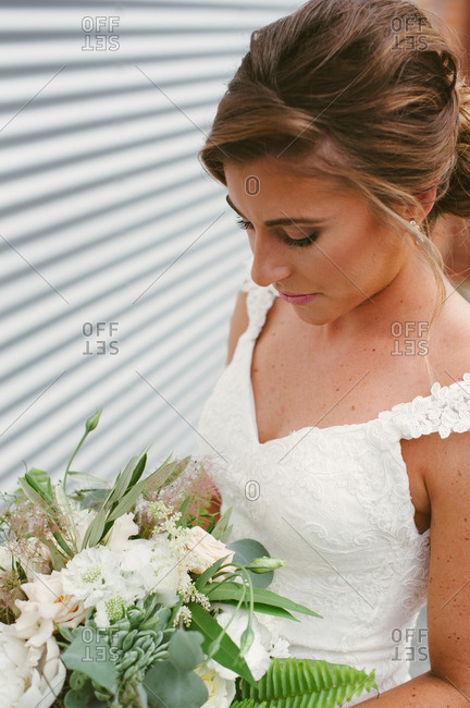 Bride in gown looking at bouquet