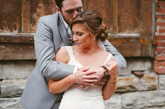 Tender bride and groom by old building