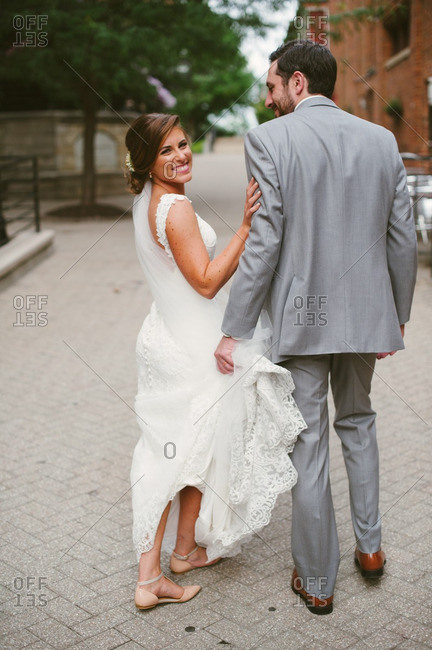 Groom holding bride's train while walking