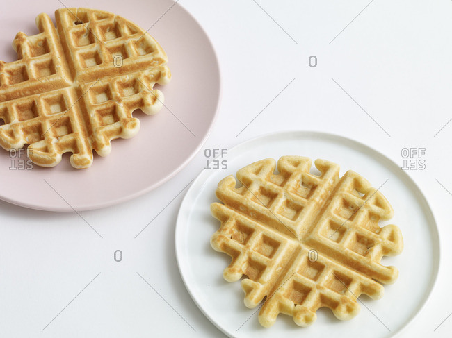 Two homemade round Belgian waffles served on plates