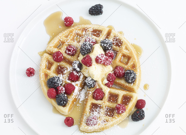 Sweet Belgian waffle served with butter, berries, syrup, and powdered sugar
